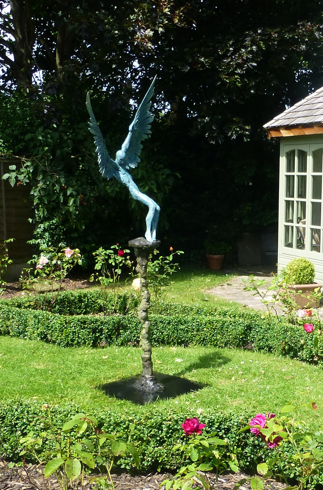 Bronze sculpture of mythological figure Icarus Falling, in garden setting.